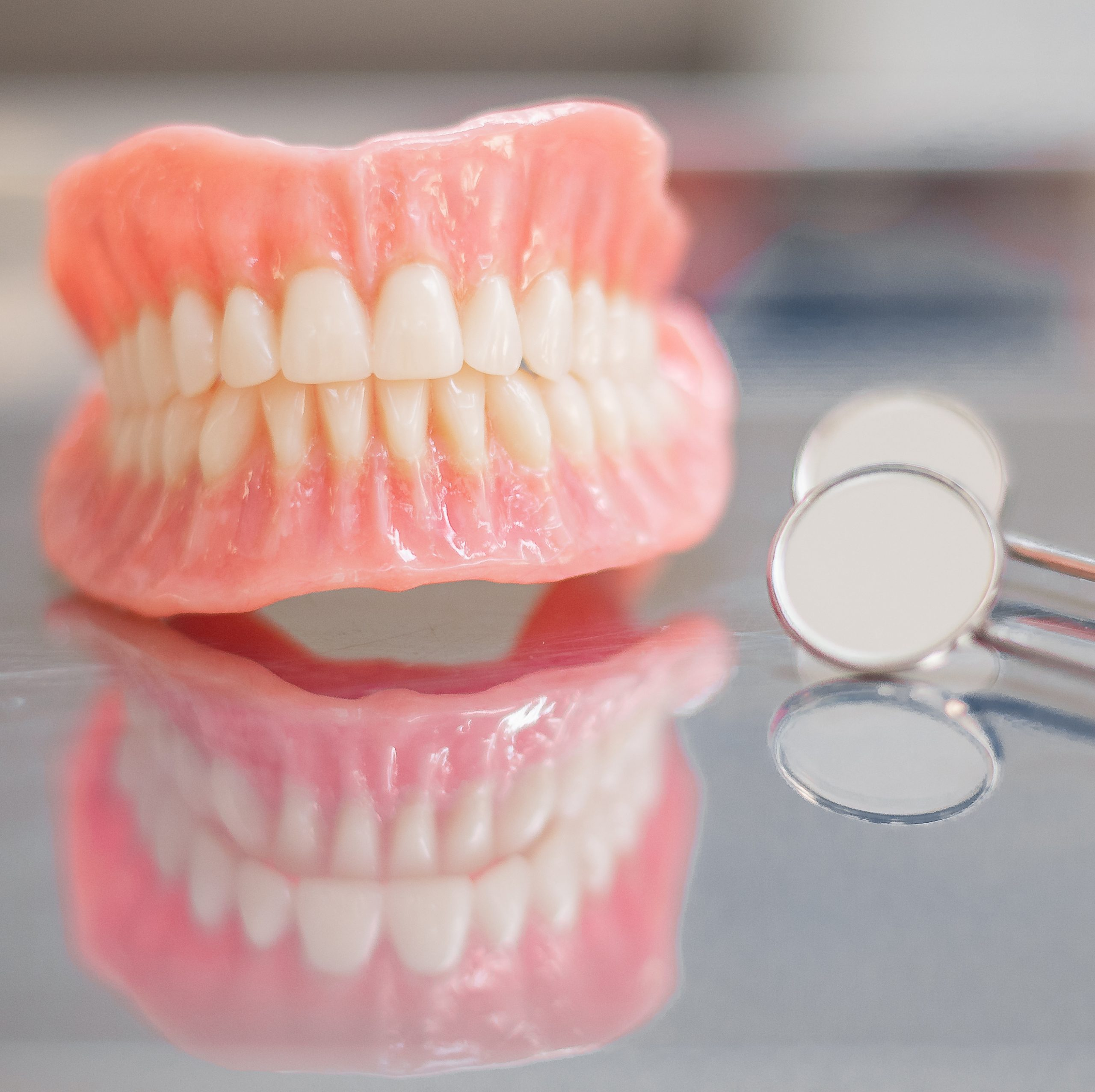 Two dentures. Instruments and dental hygienist checkup concept with teeth model dentures and mouth mirror. Regular dentist checkups